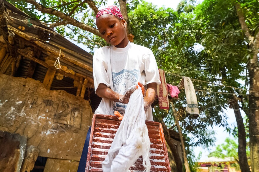 Ramatu Shellu, 8, does the laundry at her parents' home.