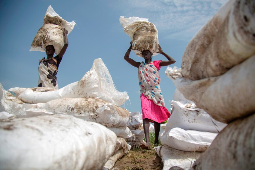 Women carry sacks of food, airdropped by the World Food Programme, this past summer in Jonglei, South Sudan.