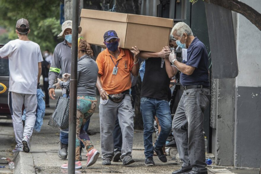 Cemetery workers carry a coronavirus victim's corpse through the streets of Guayaquil, Ecuador, this month in a makeshift cardboard coffin.
