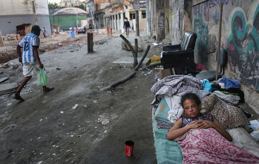 """Vanessa, currently homeless, rests on a Rio de Janeiro street on Friday where construction of a new light rail system has been delayed. The state government of Rio de Janeiro today declared a state of """"calamity"""" ahead of the Rio 2016 Olympic Games which begin August 5."""