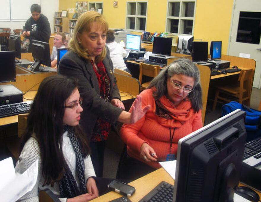Miami Beach Senior High college adviser Maria Sahwell helps Anahi Hurtado, left, and her mother fill out the FAFSA.