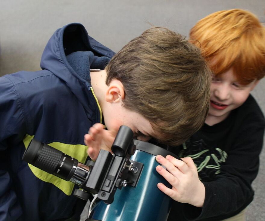 Seven-year-old Phoenix Torno checks out his own reflection in the telescope's internal mirror, while his younger brother Bodhi tries to get in on the action.