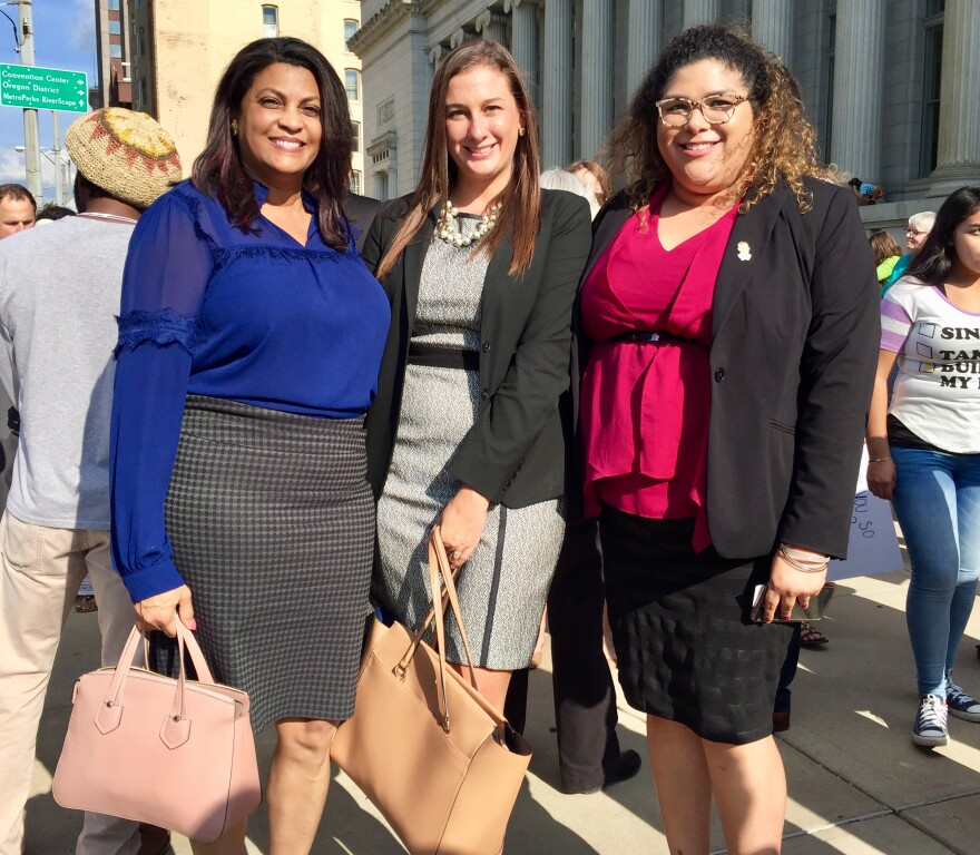 Karen Denise Bradley, left, is an immigration attorney. She's pictured with two colleagues at a recent downtown-Dayton rally in support of the DACA program.