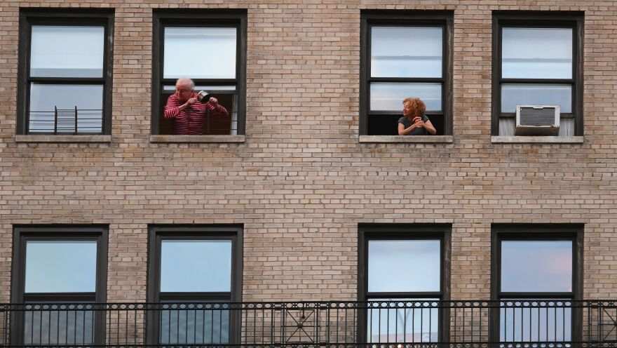 People applaud and cheer out of their windows to show their gratitude to medical staff and essential workers Thursday evening in New York City.