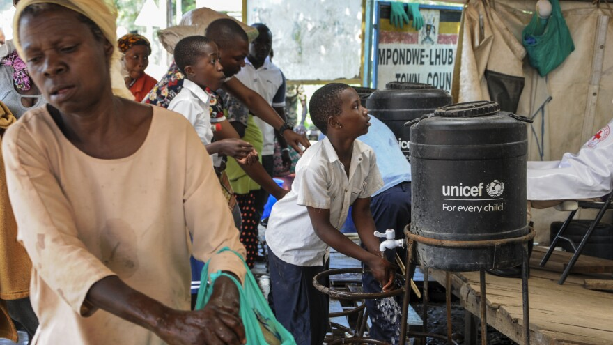 The WHO says the current Ebola outbreak is an emergency in the Democratic Republic of the Congo and the region — but not on the international level. Here, people arriving from the DRC on Friday wash their hands with chlorinated water to prevent the spread of infection at the Mpondwe border crossing in western Uganda.