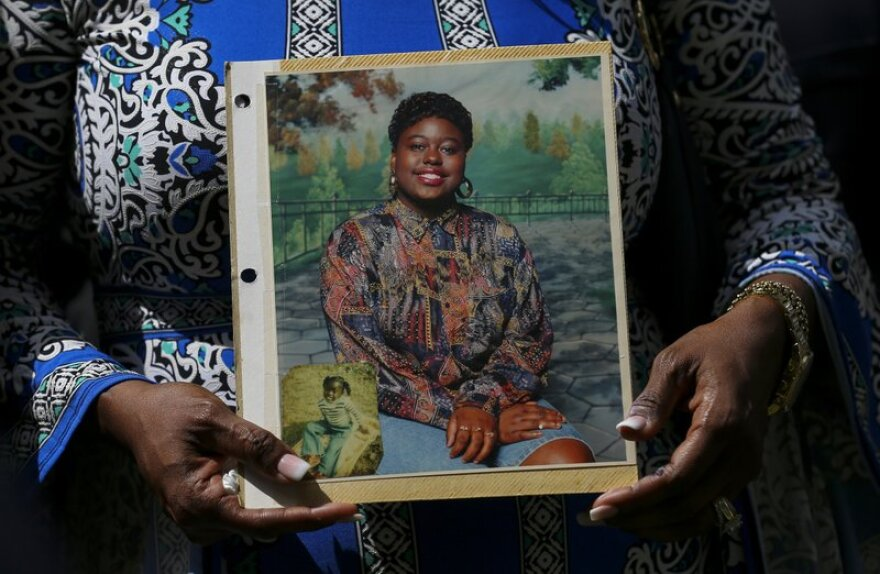 A woman holds the portrait of Pamela Turner, a woman shot by police in Baytown in May 2019.