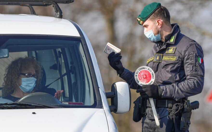 An Italian Finance guard conducts control and gives indications to drivers at a check-point at the entrance of the small town of Zorlesco, southeast of Milan, situated in the red zone of the COVID-19 outbreak in northern Italy.