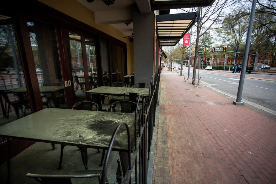 Tables sit vacant and pollen-covered at Kabab and Curry, a restaurant on Hillsborough Street during the coronavirus pandemic in Raleigh, N.C. on Sunday, March 22, 2020.