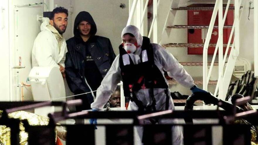 Mohammed Ali Malek (left) and Mahmud Bikhit (center) were identified by survivors as the captain and a crew member of the vessel that sank in the Mediterranean this weekend. They're seen here shortly before an Italian coast guard ship took them to Catania, Sicily.