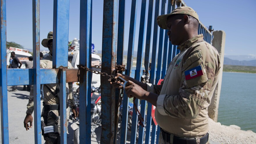 A Haitian police officer locks a gate that separates the Dominican Republic border town Jimaní from Malpasse, Haiti, last month, as Haitian authorities shut down the border because of concerns over the spread of COVID-19.