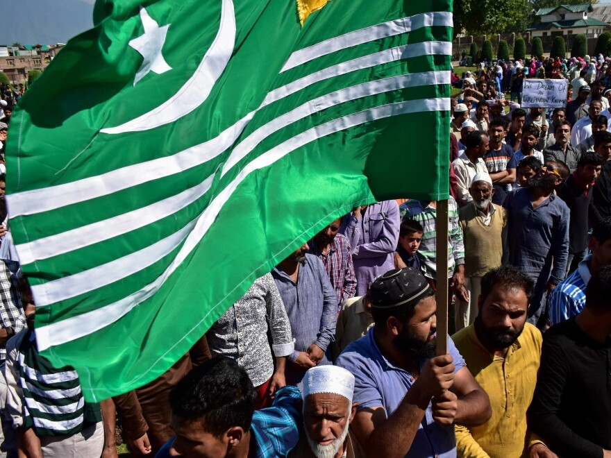 A protester holds a flag during a rally in Srinagar following the government's decision to do away with Indian-administered Kashmir's special status.