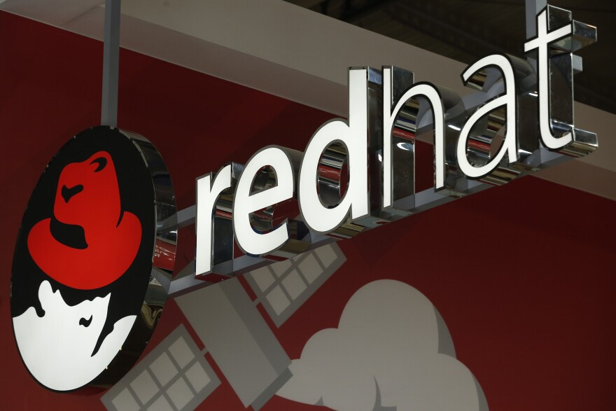 Tech giant IBM announced Sunday that it will acquire open source software company Red Hat. The company's logo is seen here at the Mobile World Congress in Barcelona, Spain, in February.