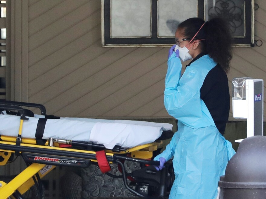 An ambulance worker adjusts her protective mask Saturday as she wheels a stretcher into a nursing facility in Kirkland, Wash., where more than 50 people were found to be sick and are being tested for COVID-19 virus.