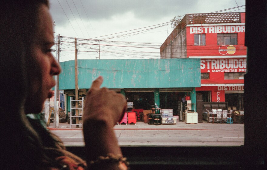 Liset points out the window of a bus while on the way to Guatemala City.