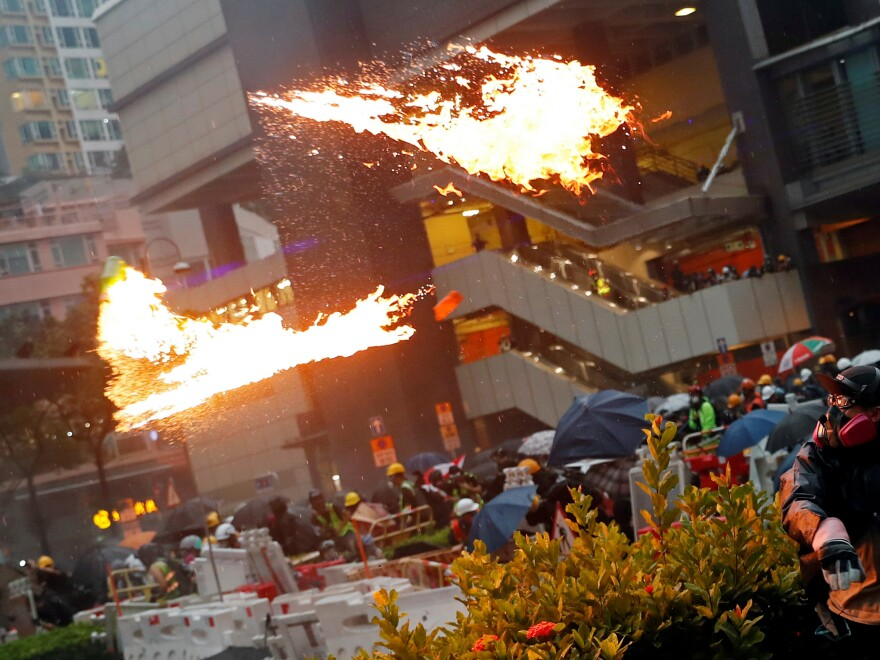 An anti-extradition bill protester throws a gasoline bomb as protesters clash with riot police during a rally to demand democracy and political reforms at Tsuen Wan, in Hong Kong, on Sunday.