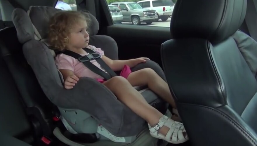 A child is left alone in her car seat