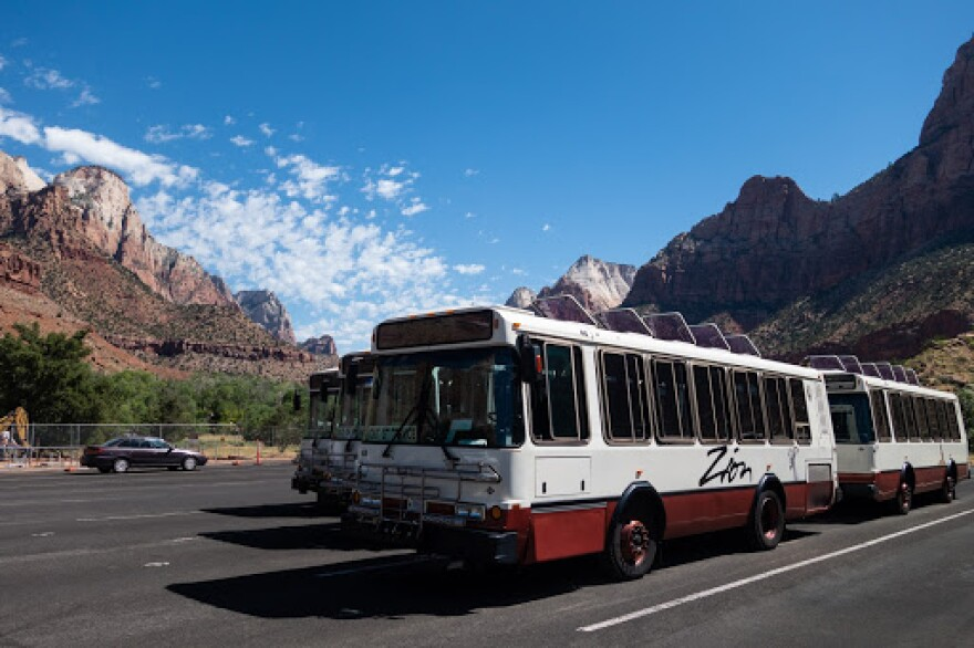 A parking lot is lined with several of Zion National Park's iconic natural-gas-powered busses. The canyon walls rise up in the background.