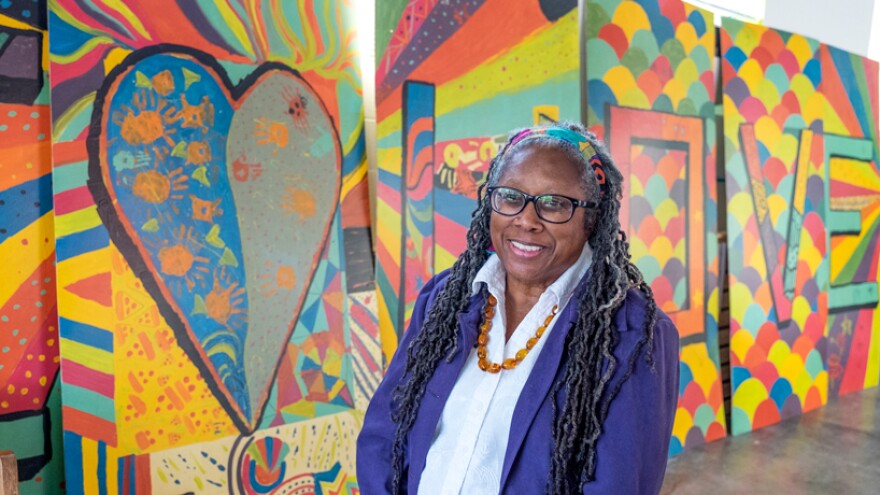 Curator Jacquelyn Lewis-Harris stands in front of a collaborative piece created in Ferguson called One Love.