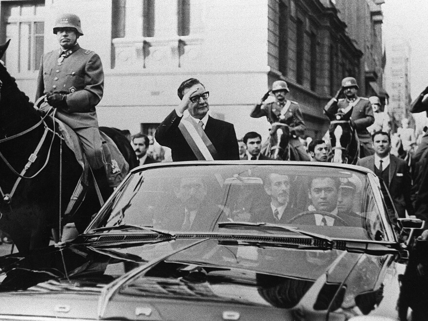 Chilean President Salvador Allende is pictured here waving to a crowd after his election victory in 1970. General Augusto Pinochet, the man who would replace Allende after a coup, and reverse his socialist policies, is on horseback. (L)