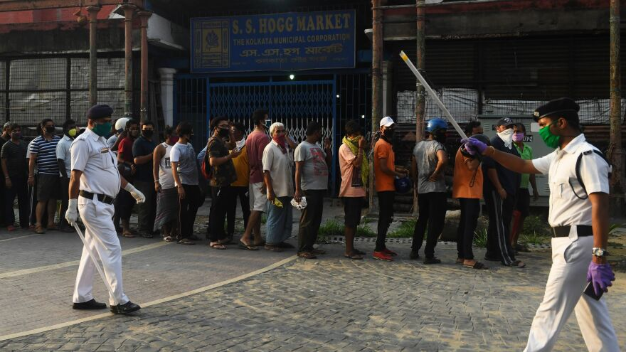 Police officials patrol as people stand in line to buy alcohol in Kolkata on Monday.