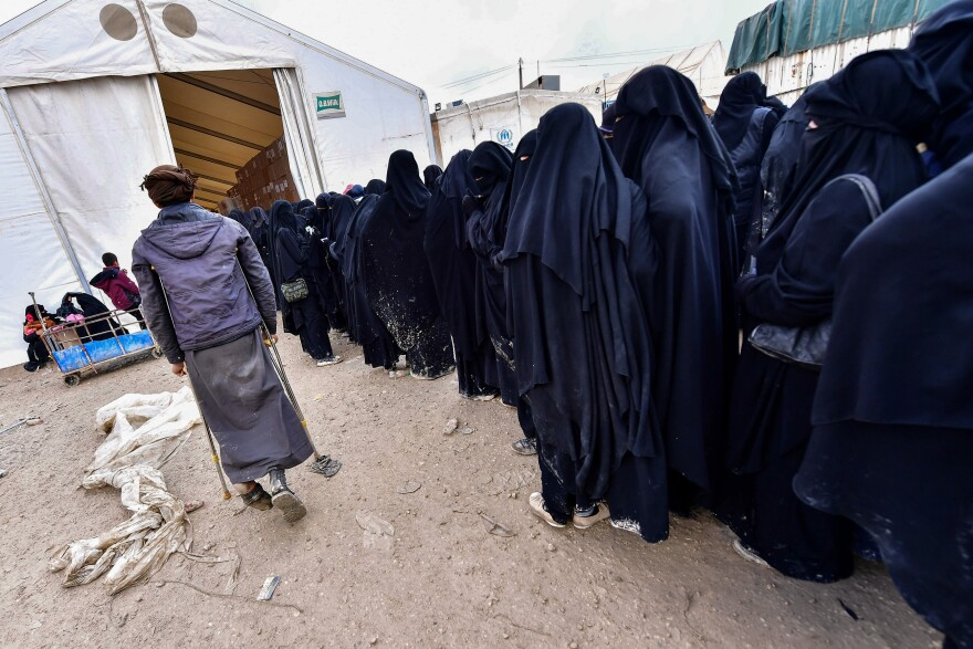 Foreign women living in Syria's al-Hol camp, where more than 73,000 people are detained, stand in line to receive goods in March. Residents lived in the former ISIS caliphate and most are children, born to Syrian, Iraqi and foreign parents.