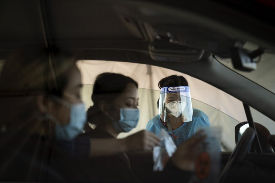 Medical assistant Linh Nguyen assists two women in a car with COVID-19 testing.