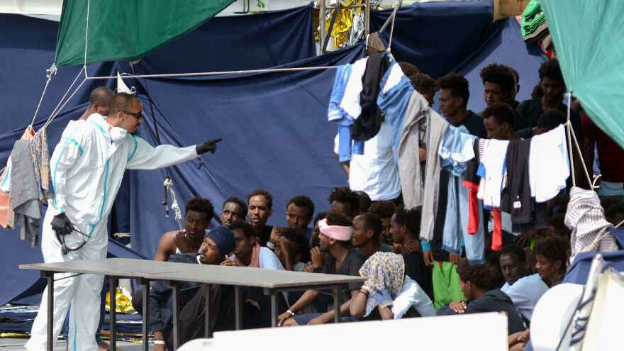 An official wearing a protective suit gestures towards migrants as they sit on the deck of the Italian Coast Guard vessel the Ubaldo Diciotti in the Sicilian port of Catania, as they wait to disembark following a rescue operation at sea.