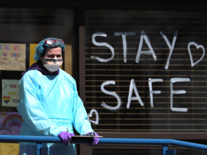 A health care worker staffs a drive-through coronavirus testing site in Jericho, N.Y., the state that remains the hardest hit by the COVID-19 pandemic. The disease has killed more than 10,000 people in the U.S., including 4,758 in New York.