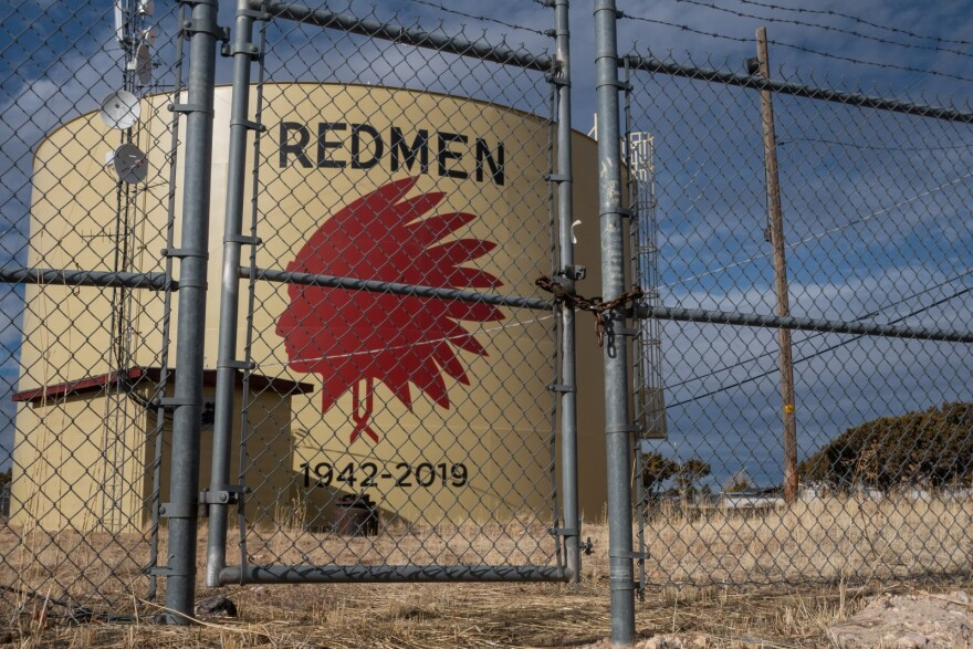 A water tank sits behind a chain-link fence, marked with a logo depicting a Native American man in a headdress.