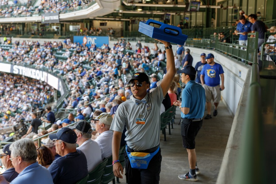 A food vendor walks through the crowd during a Milwaukee Brewers afternoon baseball game. On a national level, what were once raging baseball controversies during Selig's tenure, now are accepted parts of the game.