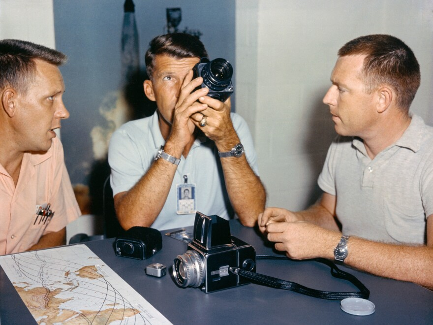 Astronaut Walter Schirra, center, checks out his spacecraft's camera equipment with Paul Becker of McDonnell, left, and Roland Williams of RCA.
