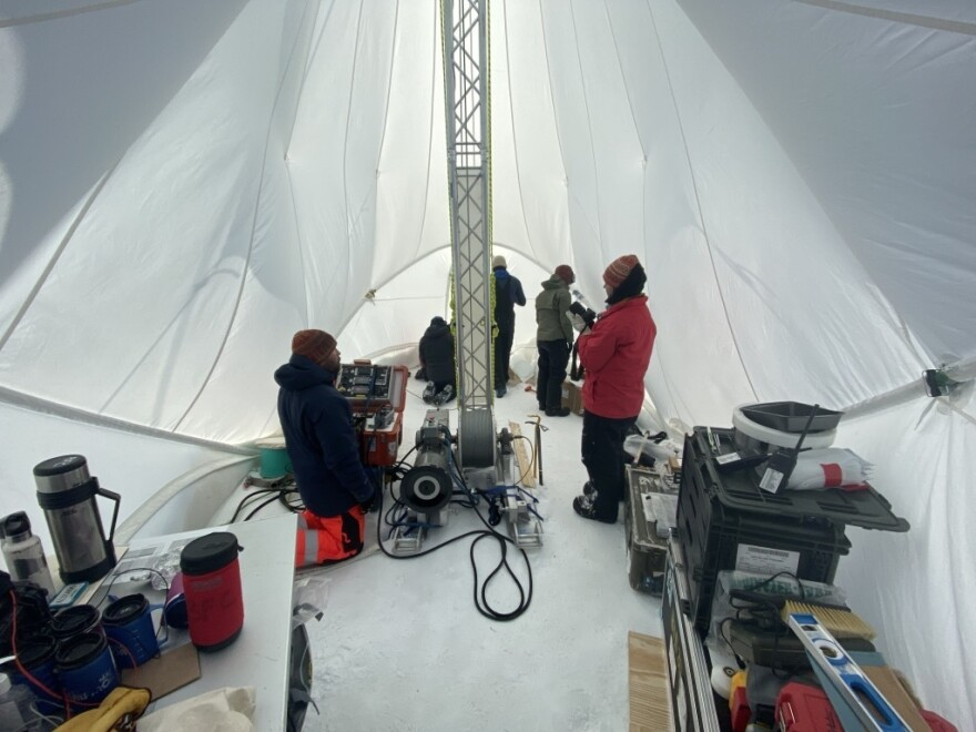 Preparing to drill Earth's oldest ice cores. Image captures the inside of the Blue Ice Drill (BID) tent with drillers Tanner Kuhl (left) and Elizabeth Morton (right). Graduate students Austin Carter, Jacob Morgan, and postdoctoral fellow Dr. Sarah Shackleton in the background. Allan Hills, Antarctica, 2019.