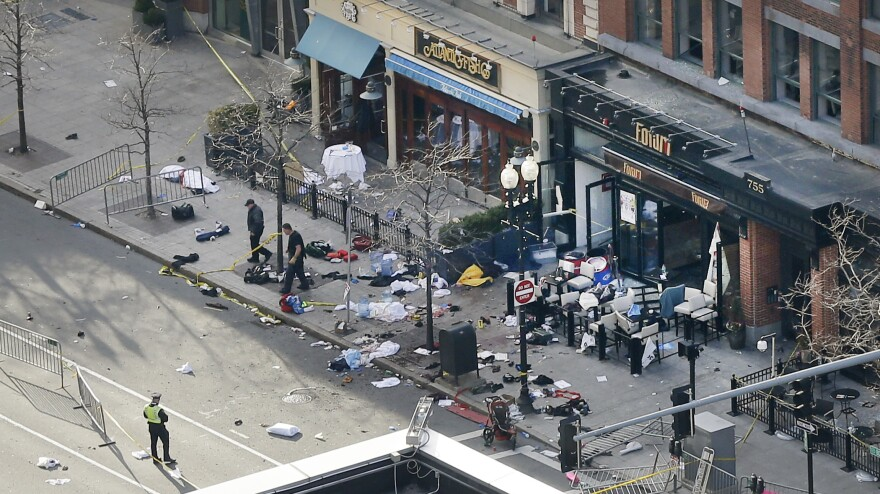 One of the blast sites on Boylston Street near the finish line of the Boston Marathon is investigated and guarded by police in the wake of Monday's attack.