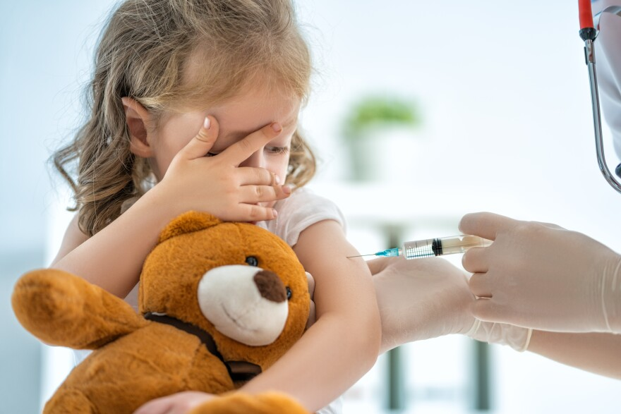 Photo of young girl getting a shot.