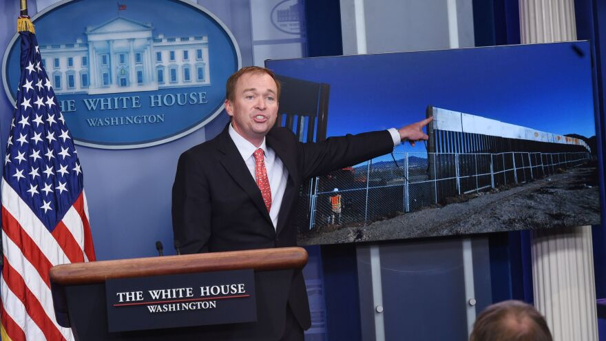 Trump Budget Director Mick Mulvaney points to an image of a border fence, making the case to reporters on Tuesday that there will be a border wall.
