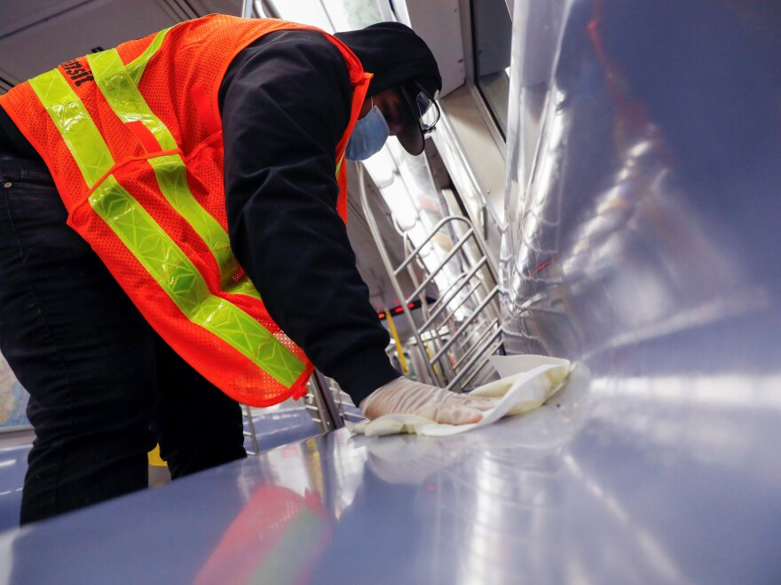 A worker wipes down surfaces on a New York City subway car to disinfect seats during the coronavirus outbreak. The CDC is clarifying its guidance on touching surfaces after a change to its website triggered news reports.