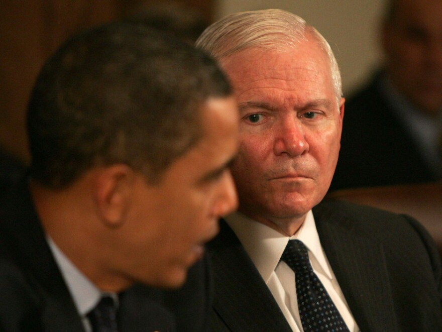 Secretary Gates listens as President Obama speaks at a Cabinet meeting at the White House. Gates began serving as defense secretary under the Bush administration, and was the first to continue under a different party.