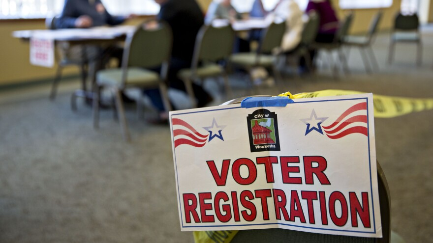 A voter registration sign hangs near a table where residents fill out paperwork at a polling location during the presidential primary vote in Waukesha, Wis., on April 5.