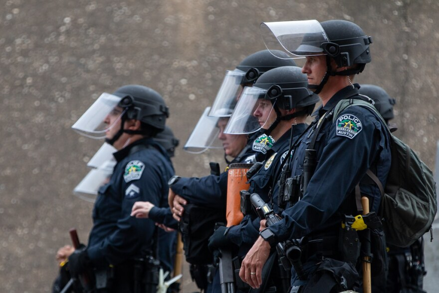 Austin police officers watch demonstrators outside APD headquarters on May 31.