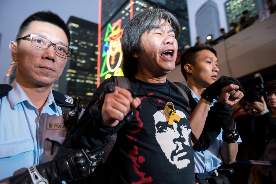 Hong Kong police arrest lawmaker and pro-democracy activist Leung Kwok-Hung during a sit-in Thursday as police clear the main protest site in the Admiralty district.