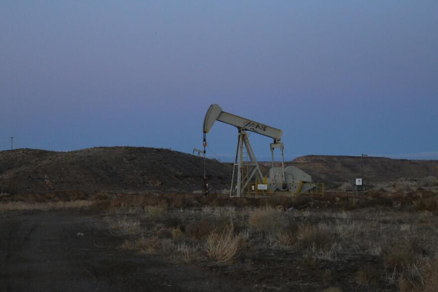 A pump jack at dusk surrounded by sagebrush