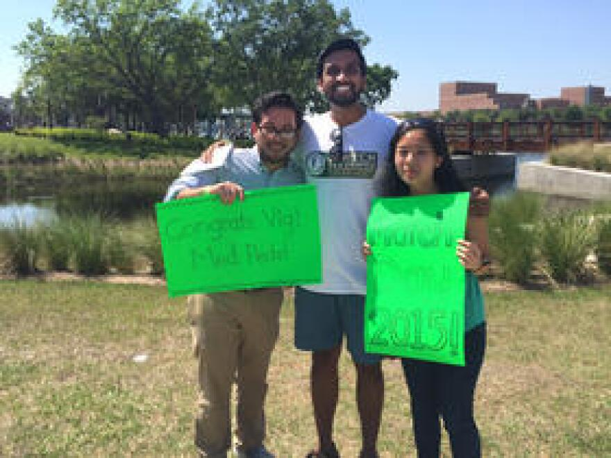 Vignesh Doraiswamy, middle, was matched to a residency program at Penn State for internal medicine and pediatrics. His friends, Juan Molina and Elaine Tan, supported him with signs.