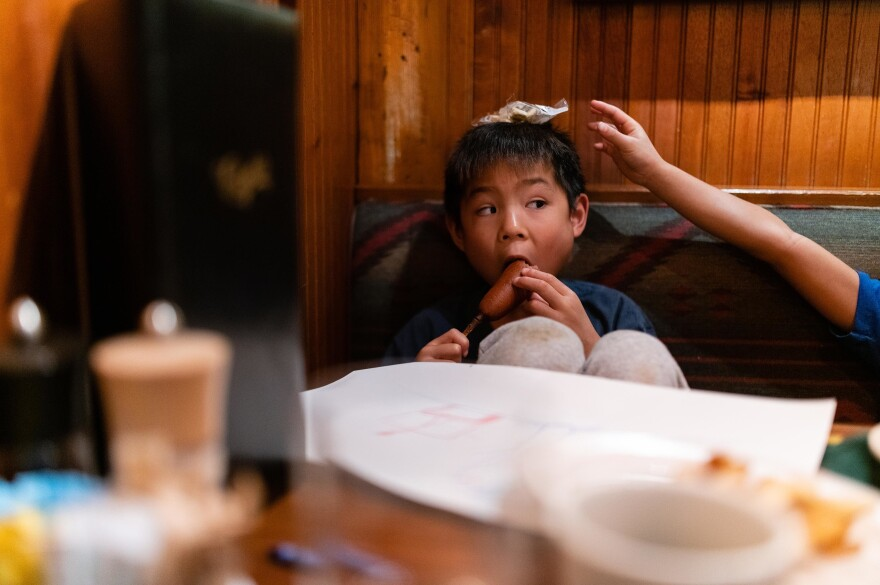 Hayle eats a corndog as Henry stacks oyster crackers on his head at Clyde's Tower Oaks Lodge in Rockville, Md., on Sept. 29, 2019.