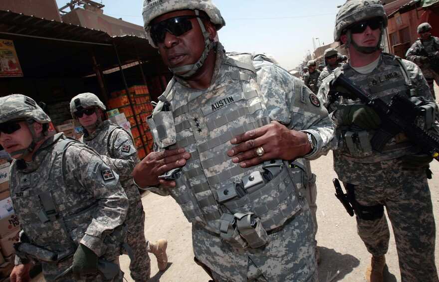 U.S. Army Lt. Gen. Lloyd Austin (center) and members of his entourage tour the Jamila market in Baghdad, Iraq, in 2008. To become defense secretary, Austin will need a waiver from Congress since he has not been out of uniform for the required seven years. He retired from the military in 2016.