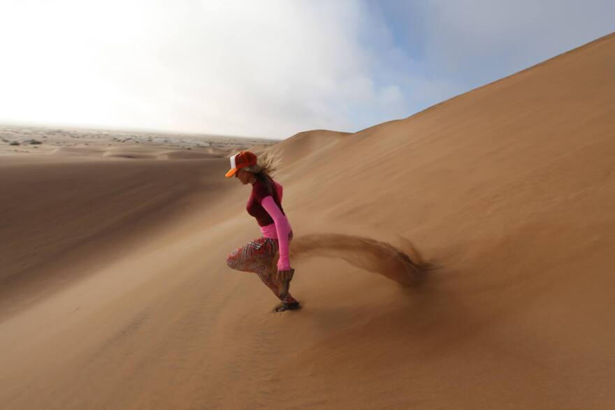 Fuchsia Claire Sims on dunes in Namibia, Africa. (Courtesy Adventure Junky)