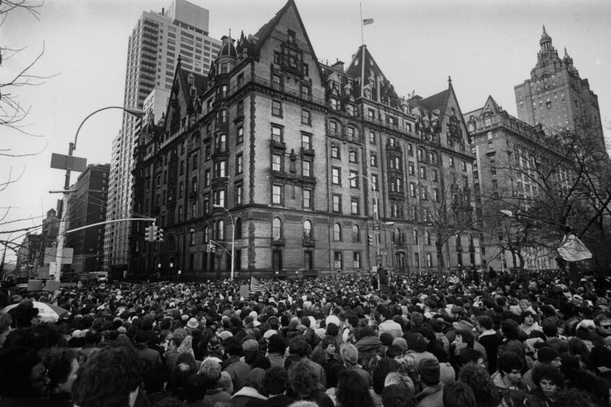 Crowds gathered outside the home of John Lennon in New York City on Dec. 9, 1980, after hearing that he had been shot and killed. A flag flies at half-staff over the building.