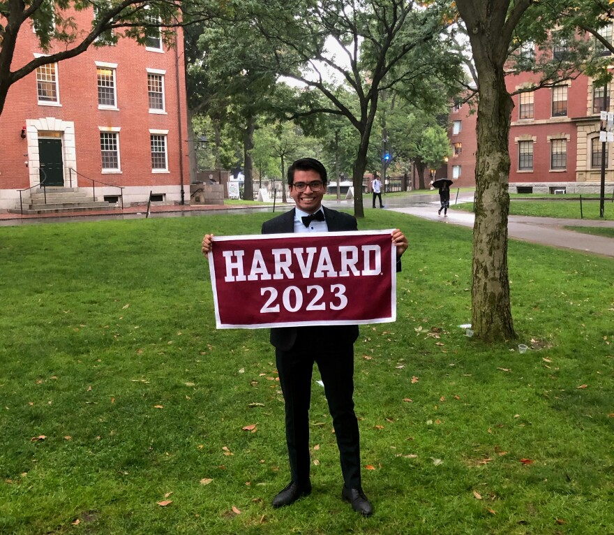 "Juan Venancio poses with a ""Harvard 2023"" banner. He is a sophomore at the school."