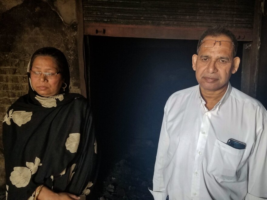 Rosia Siddiqui and her husband Mehtab Qamar stand in the charred ruins of their family business in northeastern Delhi. They ran a shop selling glass coatings here for 15 years, before Hindu mobs attacked on Feb. 25. Their shop and home were destroyed and they say they can't afford to rebuild.