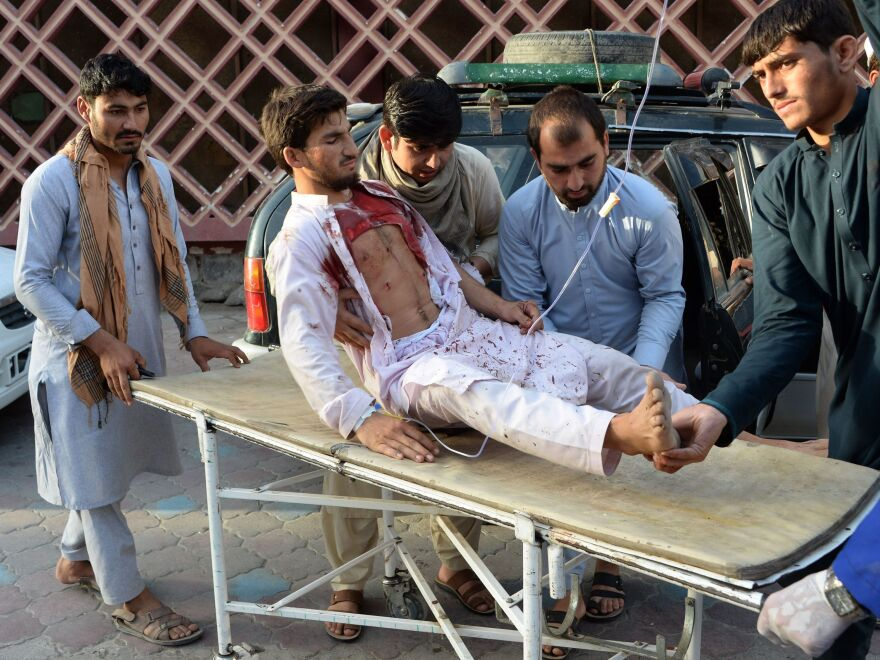 Afghan volunteers bring a man injured in the bombing on Saturday to a hospital.