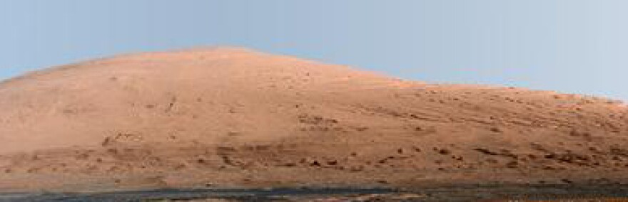 This mosaic of images from the Mast Camera on the Mars rover Curiosity shows Mount Sharp on the Red Planet's surface. The mountain, towering from the middle of a crater, is roughly 15,000 feet tall.